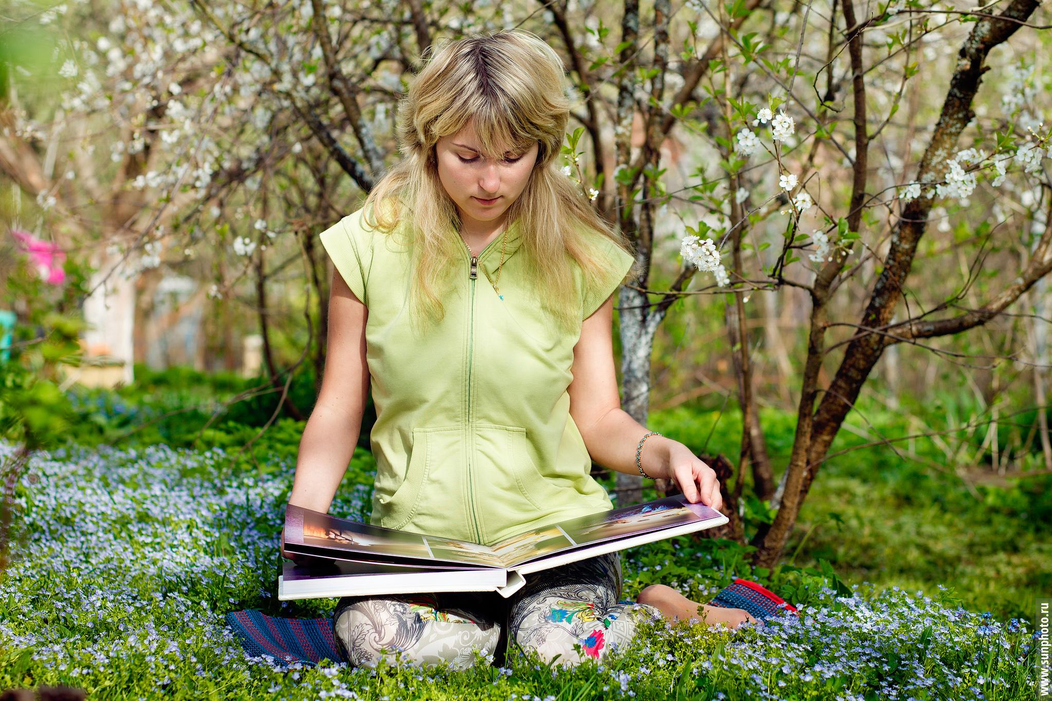 Девушка в весеннем саду держит в руках большую свадебную фотокнигу