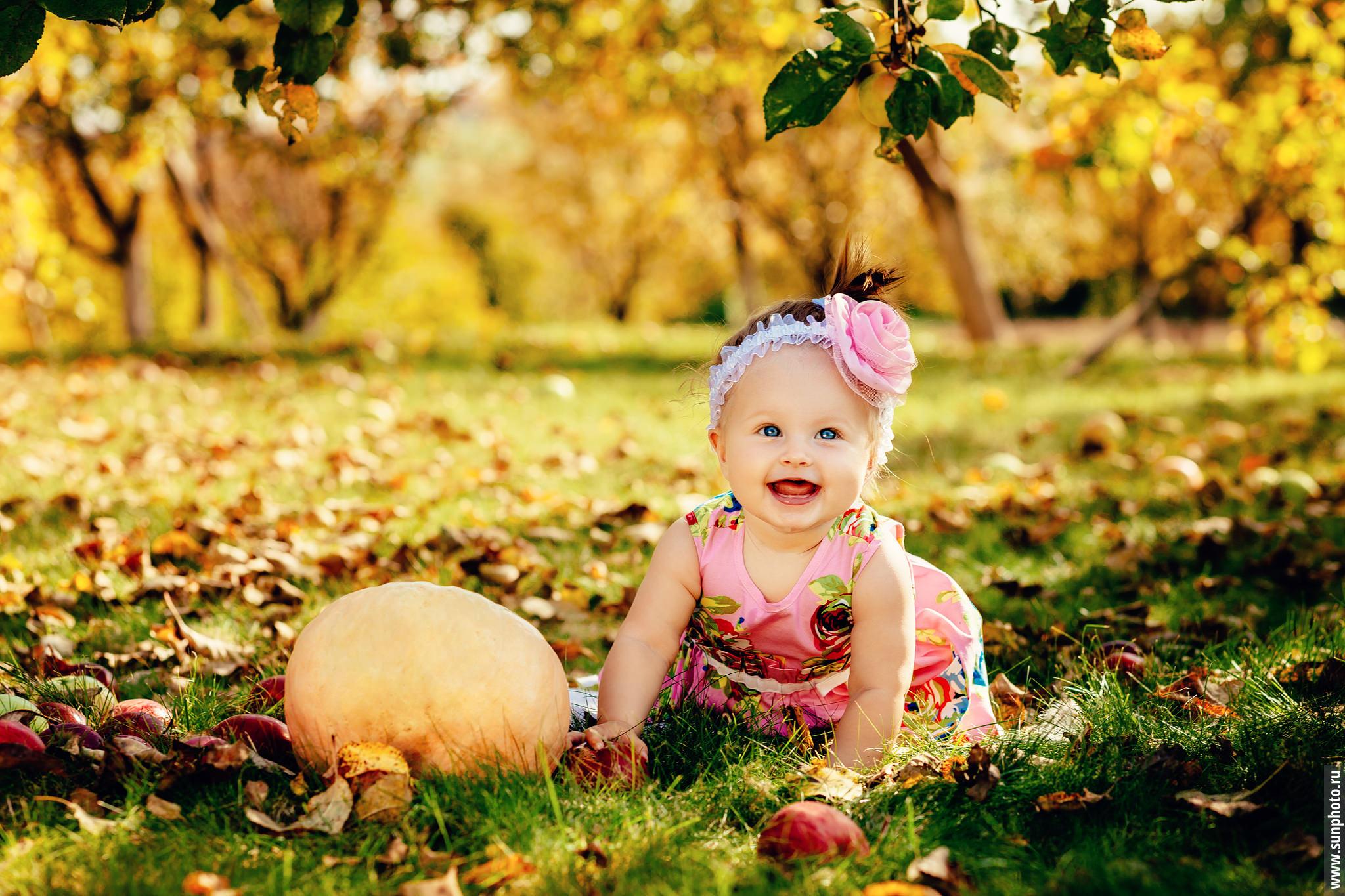 Фото маленькой девочки рядом с тыквой в яблоневом саду золотой осенью