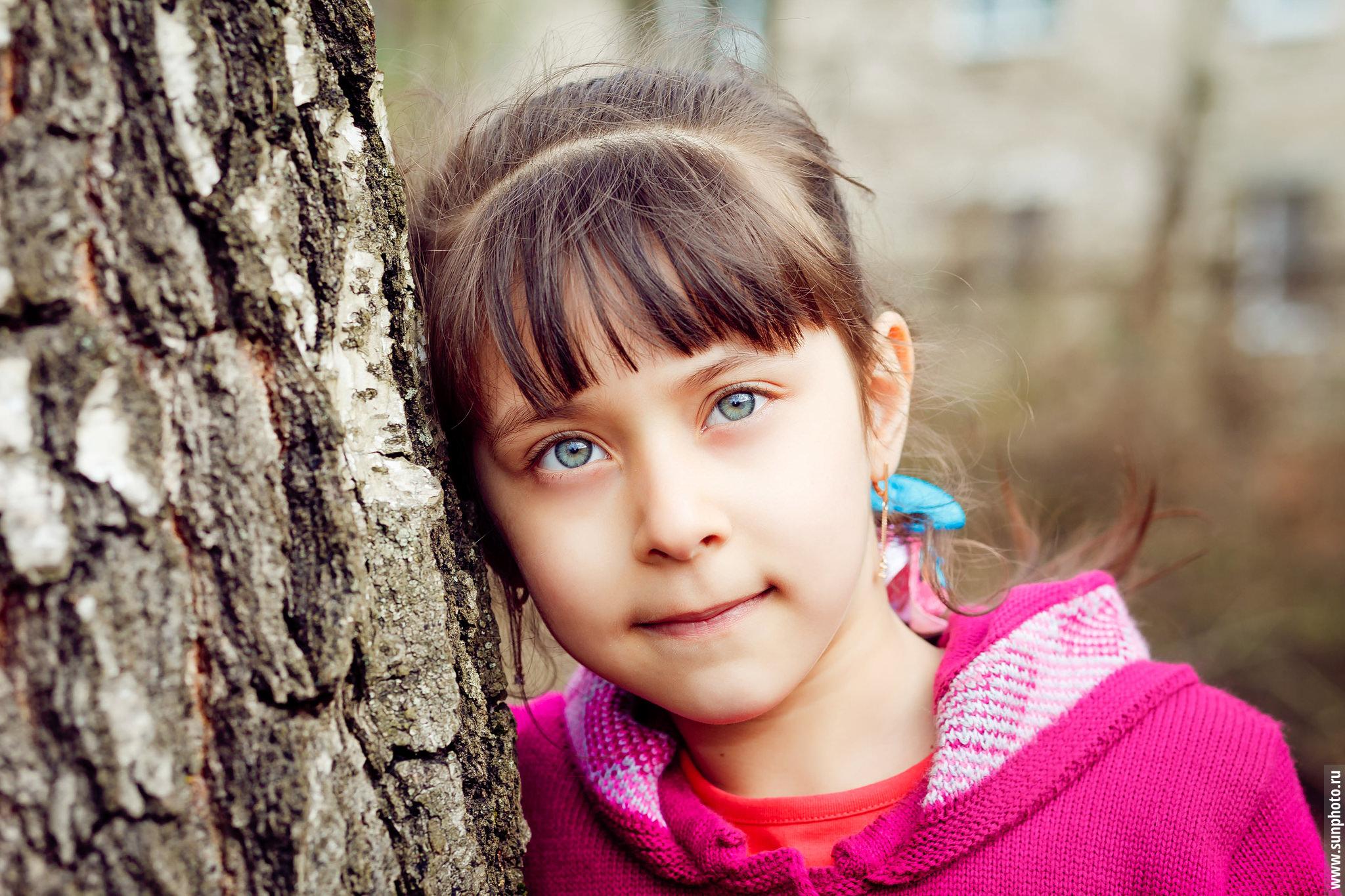 Портрет девочки в розовой кофте, сделанный во время фотосессии на улице в детском саду