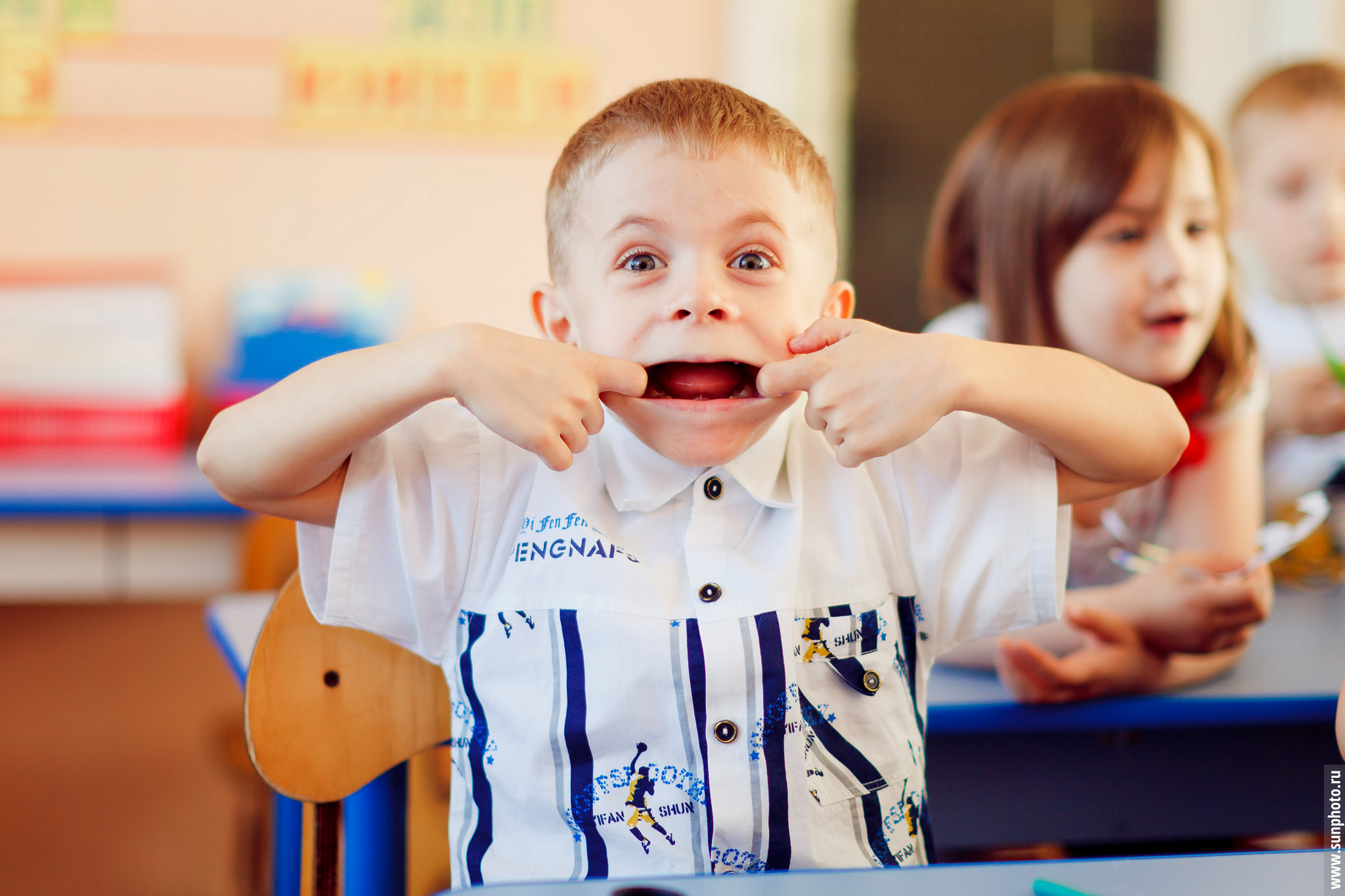 Маленький мальчик корчит рожицу во время видеосъемки в группе детского сада