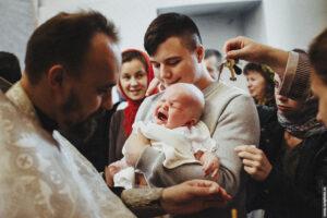 Младенец плачет во время обряда крещения